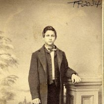 Image of TP2034 - Portrait- Young man. Standing in front of a wall painting, next to a pedestal with one arm on top of the pedestal. in a nice suit with a long jacket, vest and a tie. Not identified. Circa 1890 - 1910.