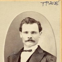 Image of TP2038 - Portrait- Man. Middle age. Wearing a dark suit with a vest and bow tie. Has a watch chain in the vest. With a moustache.
