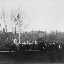Image of TP204 - Photo of the Native Daughters of the Golden West. Large group of men and women in period dress. Arbor Day Parade, 07 May 1908 parade of the Native Daughters of the Golden West. With flags flying and one large American flag on a tall pole in the court yard. Background building Macomber Cider Mill on Shaws Flat Road at the high school.