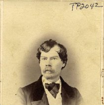 Image of TP2042 - Portrait- Man. Wearing a dark suit with large lapels and a large bow tie, with a light colored  vest. He has a full moustache with a goatee. Hair parted on side.