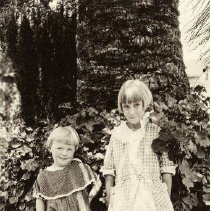 Image of TP2068 - Portrait-Children. Two children standing in a yard in front of a tree and some scrubs. The youngest child has a print dress, strap on shoes and white socks with strips. Dutch boy hair style. The older child has a checkered dress high boots and knee high socks with design on top. Dutch boy hair style. Circa 1910 - 1930.