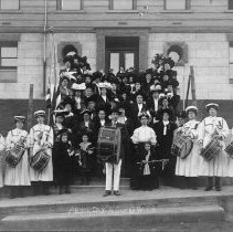 Image of TP207 - Group photo of the Dardanelle Parlor No. 66 of the Native Daughters of the Golden West on Arbor Day, March 7, 1908. The group of women, children and 1 man are standing in front of and on the steps of the Tuolumne county high school. The large group of ladies are wearing period dress with hats. There are 3 children  standing in front of the group, the smallest child is holding a baton. There's a drum group standing on the sidewalk. 6 ladies in their uniforms and 1 man with the large drum in a suit and hat.One of the ladies in the group is holding the American flag. See newspaper clipping on the back of the photo for more information.