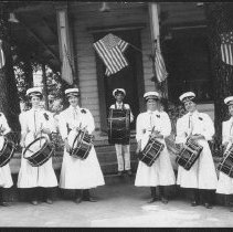 """Image of TP209 - Photo of the Native Daughters of the Golden West drum group July 4, 1907. Six ladies and one man in the middle with drums. Posed outside Bradford home on Yaney Street in Sonora. There are American flag plaques on the trees in front of the house and American flags flying from the poles on the front porch. From left to right: Mrs. Ed Rudorff, Alice Moody Woods, Daisy Mundorf, Ed Meyer in the middle with a large drum, Mrs. Chas. """"Cora"""" Rudorff and Mrs. Ed. Lander. Names of people listed on back of photo."""