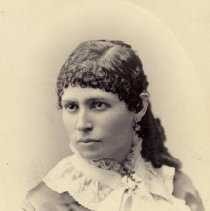 Image of TP2227 - Portrait-Woman. Dress has a large lace collar. The hair is curly and pulled back over the ears and she has earrings. Not identified. Part of the Cady Family Album.
