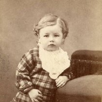 Image of TP2239 - Portrait-Small Child wearing a plaid outfit with a lace collar and lace up boots. Standing and leaning on a chair. Not identified. Part of the Cady Album Family