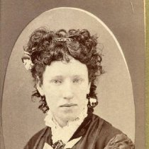 Image of TP2257 - Portrait - Woman, Not identified. Curly hair with a hair band and flowers in the hair. A dark color dress with a lace collar w/jabot and earrings. Part of the Cady Family Album.