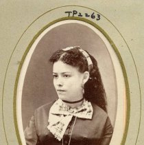 Image of TP2263 - Portrait - Young woman, not identified. Dark color dress with a plaid bow around the neck. Long curly hair going down her back with a ribbon in the hair. Wearing earrings. Part of the Cady Family Album.