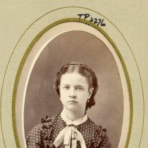 Image of TP2276 - Portrait - Woman, not identified. Polka-dotted dress with ruffles, lace around neck with a lace jabot. Hair is center parted and drawn back over the ears and has a ribbon in her hair. She has a necklace.