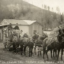 """Image of TP3269 - Dennis Guerin Driving Stage to Sonora at Mill Villa. Shows a stage coach being pulled by a team of 6 horses. Two people are riding at the top of the coach in front. One is the driver on the left and a lady on the right. There's a passenger hanging out the door window on the coach. The coach has two hanging lights on the outside of the coach in front.  The pickup station is behind the stage coach with 5 men standing outside in the front. There's a mountain in the background with trees and a small hill on the right with a fence.  On the front of the postcard at the bottom says : """" Staging"""" to Sonora, Cal. Twenty Five Years Ago. same as TP1553"""