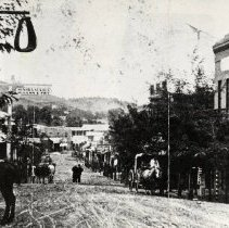 Image of TP3428 - Street Scene- Sonora, North Washington Street showing Sonora Stable, McLean and Fry photo for ad on May 31, 1873. (McLean sold out to Fry, May 1865) pictured are several horse- drawn vehicles, unidentified pedestrians, saddled horses at hitching post, two-story brick building on right foreground and trees.