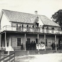 Image of TP3575 - Building-Residence of John Curtin erected fall 1880. Burned 4/25/1887. Family on top porch, L to R- Robert, Willie, Johnnie, Mike, Mr. Curtin, Mrs. Curtin, Mary, Ellen, Kate, George. Bandsmen and Ladies on lower porch. Cloudman's.