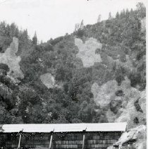 Image of TP3605 - Bridge-Covered horse Bridge over the Clavey River ( washed out in 1937) near Quilt Mills. The bridge looks like it has shingles on the side with a solid wood roof. Granite rocks are seen in the foreground. Pine trees are seen on the steep hill behind.