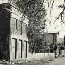 Image of TP3606 - Building, street scene, Columbia, 1930. Looking east on State St.  IOOF Building is two-story brick with three iron doors in front.   Ruins of Tuolumne Engine No. 2 Fire-House, General Merchandise Store, Old saloon.