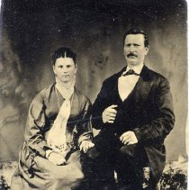 Image of TP3612 - Portrait- Man and Woman. Not identified   Circa 1890's.  Both are seated.  Her hair is pulled back with a part in the center.  Her long dress has long sleeves and pleats on the hem.  A scarf is around her neck  with the ends hanging down her chest.  He is wearing a suit with a white shirt and bow tie.