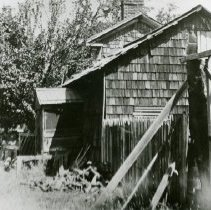 """Image of TP3660 - Building - Exterior - """"Mr. Chamberlain in front of Home."""" Second Garrote.  The home has a brick chimney.  The sides have shingles.  There is a pile of wood for burning at the corner of the home.  Large trees are shading Mr. Chamberlain standing toward the back of the home."""
