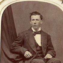 Image of TP3869 - A Black and white portrait of an unidentified man with dark hair, side part black jacked and plaid pants. shirt and bow tie. Album #11 Sewell Collection.
