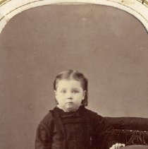 Image of TP3884 - A Black and white portrait of an unidentified small child standing beside a velvet stool with fringe. Album #11 Sewell Collection.