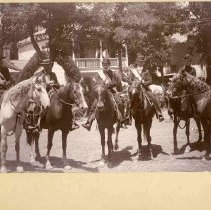 Image of TP401 - July 4, 1901 Celebration. A group of six people on horses - 4th from left is Chas. Haws. There are 2 women and 4 men. Buildings, trees and people are in the background. All of the riders are wearing sashes. The women are in long black dresses, wearing bowler hats and riding side-saddle. The men are wearing suits. two of them have bowler hats, one has a straw hat and the other one has a cowboy hat. Two of the men have mustaches.