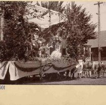 Image of TP403 - An Elks lodge float made in celebration of the 4th of July in 1901.  Men and women in costume are on the float. The women are seated.  The float is on a trailer being pulled by horses. Tarps are hanging down the outsides of the trailer and are on the horses.