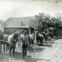 Image of TP4207 - Mike Curtin (Buchanan Mine) and team in front of Pat Burke's blacksmith and carriage shop on Washington Street. Lee Price is on the saddle horse behind the team. The Blacksmith is Jim Farnham.  Lee Price on saddle horse. The freight on the wagons is probably destined for the Buchanan Mine southeast of Tuolumne.  Jim Farnham blacksmith Hartness children