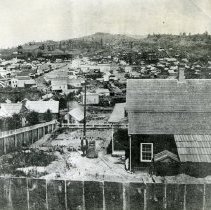 Image of TP4821 - Landscape - Looking north from Maiden Lane across Main Gulch about 1860 Columbia. Unidentified man and woman standing in backyard of a home.