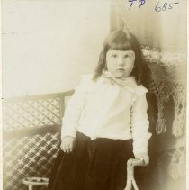 Image of TP685 -  Unidentified young child, probably a boy, dressed in dark full trousers and white shirt standing on chair.  He has long shoulder length hair with straight bangs.
