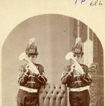 Image of TP686 - Two unidentified boys with horns, posed standing next to chair, in band or concert uniforms.