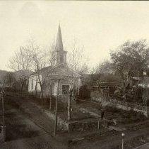 """Image of TP766 - A 6-1/2"""" x 8"""" Black and white photo of the Methodist Episcopal Church, Sonora. Reverend Martin Judy for 1903-1906. Notes say that the church was torn down in either 1920 or 1922. It also says that Wells planted palm trees in Simms yard.  The front yard of the church has wall on both sides and in the front with steps going up to the walkway. The side yards are fenced in with trees in them. There are trees in the front and a man standing on the walkway ( might be Reverend Martin Judy). There's power lines in the photo.   There's roads on the left of the church and in front. The road on the left goes to some homes in the back of the church.  are"""