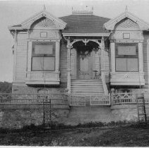Image of TP790 - J.A. Van Harlingen home in Sonora. Built in 1893 or 1894. Brick wall with a metal fence on top and 2 gate at the entrance. Two trees just planted in the front with support frames around them.