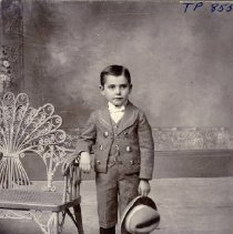 Image of TP855 - Young boy, Dressed in a suit with a vest with a watch bob, short pants, boots, knee socks and White bow tie holding a matching hat. Standing in the studio on a fuzzy rug with his arm on the edge of a antique bench.