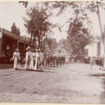 Image of TP89 -  Sonora parade, 1898. Street scene of parade, group of women in white dresses with dark sashes in foreground, men in uniform carrying American flag behind followed by others.Sonora Express and Transfer can be seen on the right of photo, City Livery Office can be seen on left.
