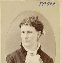 Image of TP977 -  Portrait - Unidentified Lady. Pocket size photo. Dark dress with a lace jabot with brooch. A flower in hair. Hair pulled back in a ball.