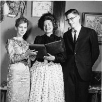 Image of TP113 - Group photo, black and white. Three people, two women and one man. Tuolumne County Historical Society Lamplight Dinner 1968. Left to right - Frances Heron, Dottie Firebaugh is holding the book and is period dress, Kris Larsen.