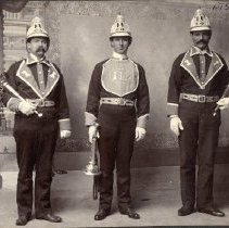 Image of TP520 - GROUP- L TO R. 1. BILL HARRINGTON 2. CHARLES HOWES 3. VASSO TERZICH IN FIREMEN UNIFORMS, SONORA FIRE DEPT #1. Circa early 1900's.