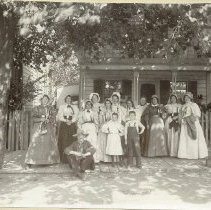 Image of TP1162 - GROUP - H. M. Morris at Stockton N.D.G.W. group.  From left to right standing - May Gibbons Sobranes, Ellen Carroll, Mary Mendosa Guerena, Jessie Simpson (Patterson), Kitty Kenney Hartvig, Frances Riordon Rehm, Mrs. Ellis Wilzinski, Mary Monohan Patrick, Miss. Maggie A. Fahey, Tillie Keil Hender and Hannah Gibbons Shine. Seated is Joe Durkin, Children standing Inez Guerena Meyers and Johnnie Patrick (Partville?). There's 2 ladies on the porch of the house behind the group. the group is in early period dress.