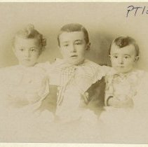 Image of TP1220 - Dentone Children, black and white portrait, vignette, three young children, boy in center wearing dark jacket with large white overcollar, younger children on either side in white or light dress.