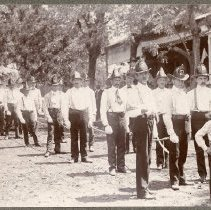 Image of TP783 - PHOTO OF THE 4TH OF JULY 1903 PARADE IN COLUMBIA. COLUMBIA ENGINE COMPANY #2. THERE PULLING AN ENGINE THAT IS DECORATED AS A FLOAT. LEFT To RIGHT - 1. JOHN BRADY 2. JOHN BACIAGALUPI 3. WM. KRESS 4. JIM MILSPAUGH 5. EMIL NELSON 6. PAUL NJIRICH 7. PHIL. HAGEMEYER 8. ANDY PAGE 9. TOM O'HARA 11. HENRY MILLER 12. CLARENCE NEU 14. DAVIS 15. FRANK LAVIN.  JOHN PODERTA IS THE LARGEST BOY IN FRONT OF THE GROUP ALONG WITH 3 OTHER BOYS. HARRY DAVIES IS STANDING BY THE TREE IN THE REAR, FLOSSIE DAVIS KELLY IS THE 2ND LADY AT THE SIDE, GERTRUDE MORGAN IS THE LAST LADY.  William Wax's universal art studio and attached dwelling were built at the southeast corner of Main and State Streets, Columbia in December 1900. This was the site of the Colombo Saloon for many years from 1876 - 1888. The Columbo restaurant. Information from Barbara Eastman - June 1961.