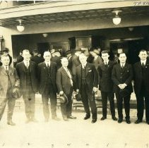 Image of TP816 - Group Photo, In front of Sonora Theater. 3.Senator J.B. Curtin. 7. Archie Stevenot, and  8. Charles H. Segerstrom Mother Lode Highway Meeting in Sonora November 18th, 1922. Theater sign on the outside wall of the theater saying, HO DAVIS THE SILENT CALL next to a ladder leaning on the wall.