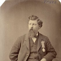 Image of TP882 - PORTRAIT- A.O.U.W., G.C. BAKER, 1884. SUIT WITH VEST, WATCH CHAIN. RIBBON ON THE JACKET. BOW TIE, FULL BEARD AND MUSTACH. CURLY HAIR PARTED ON THE SIDE. STANDING IN THE STUDIO LEANING ON A CHAIR WITH ONE ARM BEHIND HIS BACK.