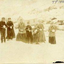 Image of TP1446 - Anna Bauman and unidentified group, photo is taken with subjects standing in snow in front of several buildings, and rocky slope. 7 people, women and men and children dressed for the cold weather,