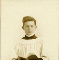 Image of TP1569 - Photo of a young boy in an Alter uniform holding an opened book in front with both hands. The photo is in a parchment jacket.