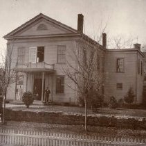 Image of TP1825 - Tuolumne County Courthouse built in 1853, pictured on front porch :Eugene Abbott, County Tax Collector, unidentified man and woman, photograph reveals large white wooden clapboard sided, l-shaped building. Front porch with balcony in center front, landscape is raised and leveled, young trees are visible, small stone wall across the front landscape. several six over six windows are visible. One photo mounted on board, second unmounted. credited to Harrington Studios