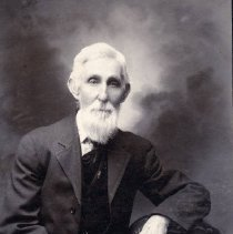 Image of TP2481 - GEORGE ETHELL.  He is sitting in a chair wearing a suit jacket, dress shirt and tie.  A watch fob can be seen  He has a large ring on his little finger, left hand.  He has a full bread.