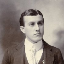 Image of TP3276 - PORTRAIT-BERT MOORE. Wearing a suit with a vest. Watch chain is going across the vest from pocket to pocket, with a bob in the middle. High stiff collar wit a white striped tie. Two pins are on his lapel. One is of a person, the other is a triangle with a bear on top and a star hanging at the bottom. Short hair parted in the middle.