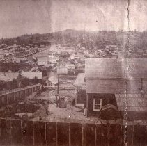 Image of TP2802 - A black and white landscape photo of Columbia.  Photo shows residence with fence surrounding it and an unidentified man and woman standing in yard. c.1862