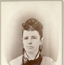 """Image of TP10351 - A 6.5"""" x 4-1/4"""" Black and white portrait of Mrs. Frank Norton wearing dress with high pleated collar and is wearing a necklace, hair is pulled back with curls parted in middle."""