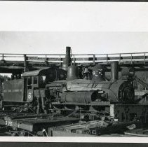 Image of P33117 - West Side Lumber Co. Shay engine #6 in the mill yard in Tuolumne, California. Looks like winter storage. Empty log cars in foreground, log pond to rear.