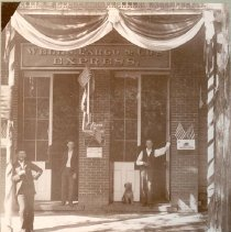 Image of SPV10030 - A black and white photo of the Wells Fargo Building, Sonora CA.  George Banks is right doorway; Edwin Bray? is loft doorway; and Ed Doyle is on sidewalk.