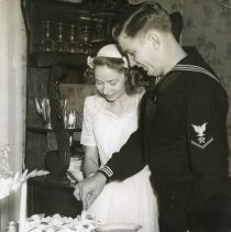 Image of TP15522 - A black and white photo of Ben & Betty (Burgson)Robinson, bride and groom. Ben a WWll sailor. Ben and Betty cutting the wedding cake.