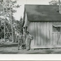 """Image of P36888 - A 3-1/2"""" x 5-1/2"""" Black and white postcard. Mr. Lawrence Crandall and Mr. Frank Zimmerman at old Mt. Elizabeth tower and cabin. Mr. Crowe developed it, September, 1931."""